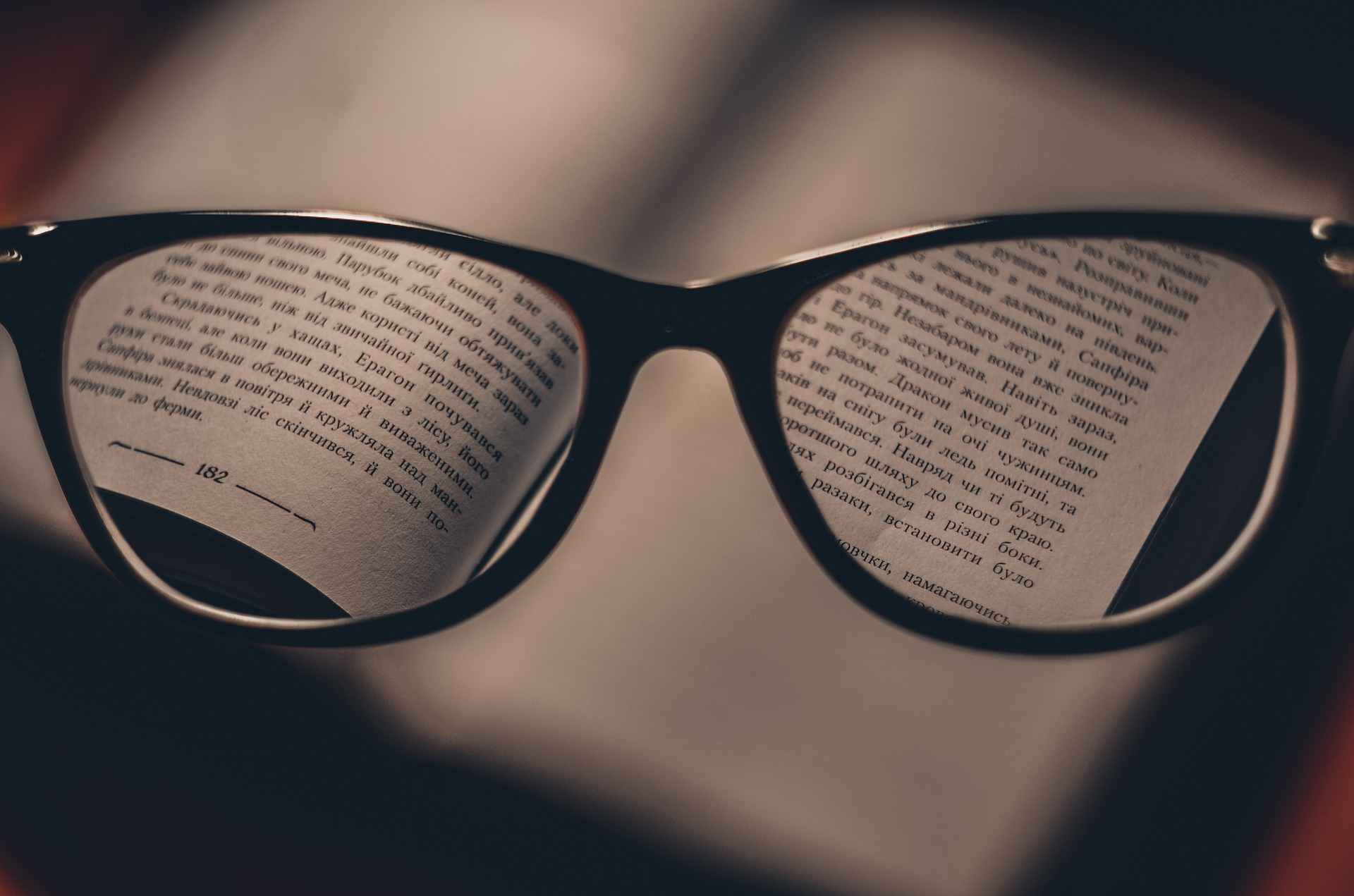 A book trough glasses - only part of the text is in focus.
